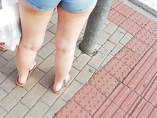 Candido adolescente in età legale che cammina in pantaloncini blu sul centro commerciale pa