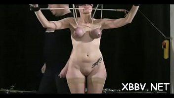Une femme déshabillée se tient ligotée et endure un énorme esclavage mammaire