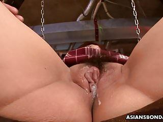 Fastened up oriental schoolgirl has her squirting bush viciously to