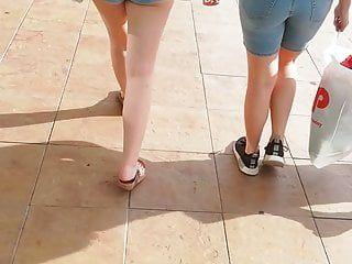Candid adolescente in età legale che cammina in pantaloncini blu nel centro commerciale