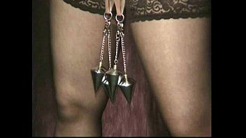 Priest puts a metal chain with enormous weight on pierced cookie lips of villein and spanks her